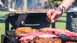 man pouring seasoning on the grilled meat